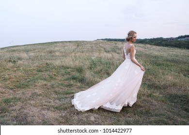 Young woman in a white dress is standing on the field. Portrait of girl outdoor. Romantic young woman posing on the background of sunset sky.