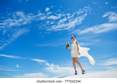 Young woman in white dress standing on a hill against a blue sky