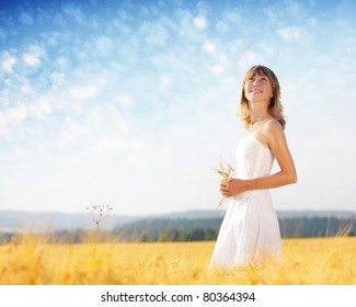 Young woman in white dress standing in the middle of a field with yellow ripe wheat