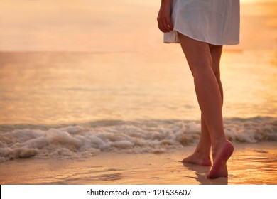 Young woman in white dress walking alone on the beach in the sunset