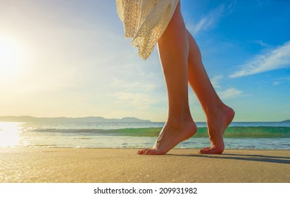 Young woman in white dress walking alone on the beach in the sunrise. Closeup detail of female feet and golden sand on beach.