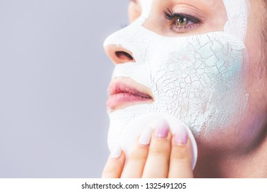 Young woman with white dried mud mask on face being removing cosmetic with cotton swab. Teen girl taking care of oily skin. Beauty treatment. Skincare.