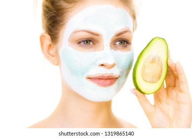 Young woman with white green mud mask on face holding avocado fruit. Teen girl taking care of her skin, cleaning the pores. Beauty treatment.