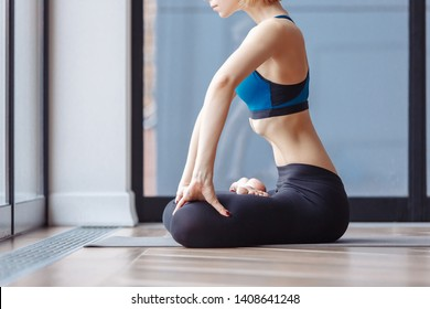 Young woman in white gymnastic suit makes vacuum exercise for muscles internal organs of abdomen sitting on floor at home. Padmasana, Lotus Posture, performing Upward Abdominal Lock, Uddiyana Bandha