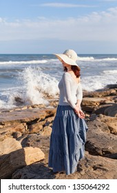 A young woman in a white hat is watching  waves.