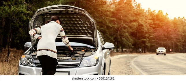 young woman in a white jacket standing near the broken car. The girl opened the hood and look at the engine. Refit woman car