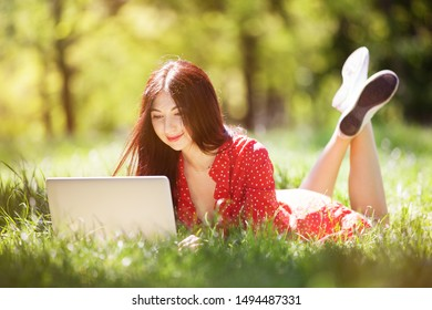 Young woman with white laptop in the park. Beauty nature scene with colorful background, trees at summer season. Outdoor lifestyle. Happy smiling woman with computer lay on green grass