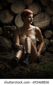 Young woman in white lingerie and boots, sitting at a stack of wood