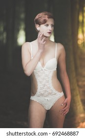 Young woman in white lingerie posing in a forest
