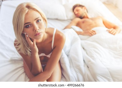 Young woman in white lingerie is sitting on bed and looking at camera while her partner is sleeping in the background