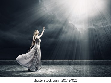 Young woman in white long dress reaching to light