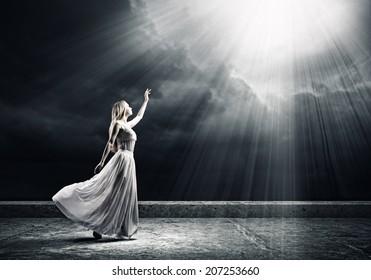 Young woman in white long dress reaching to light