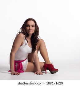 Young woman in a white mini dress, red high heels with a pink scarf sitting on the floor