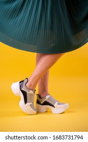 Young woman with white modern sneskers with dark green skirt  on yellow background isolated