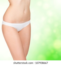 young woman in white panties posing against green blurred background