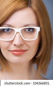 Young woman with a white plastic glasses keeping an eye contact.
