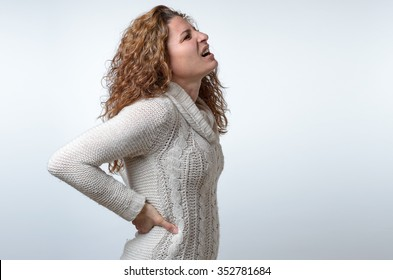 Young woman in a white pullover with back ache clasping her hands to her lower back as she looks up wincing in pain, side view