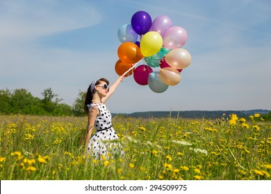 young woman with a white rockabilly dot dress and a lot of colorful balloons in the meadow