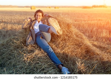 A young woman in a white shirt, beige coat and jeans  enjoys nature, sitting on a haystack around blue sky. The concept of livestyle and outdoor recreation in autumn