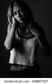 Young woman with a white shirt. Black and white. Low key
