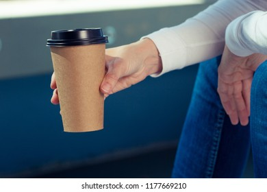 Young woman in white shirt with disposable coffee cup. Youth, modern lifestyle. Coffee break, cosy relaxing moment.