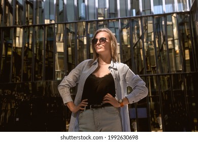 A young woman in a white shirt in light pants and sunglasses poses in the mirrored courtyard of the business center, illuminated by the sun's rays. Reflection in the mirror. Business portrait. - Shutterstock ID 1992630698