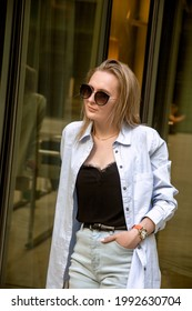 A young woman in a white shirt in light pants and sunglasses poses in the mirrored courtyard of the business center, illuminated by the sun's rays. Reflection in the mirror. Business portrait. - Shutterstock ID 1992630704