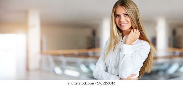 Young woman in white shirt standing in the corridor of business center