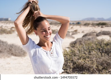 Young woman in a white shirt is standing on the beach and holding her hair above her head in a pony tail