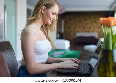 Young woman in white shirt typing on laptop at home, online communication