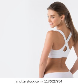 Young woman in white sport lingerie looking in profile . rear view , copy space for text