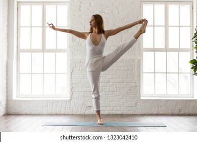 Young woman in white sportswear, pants and top practicing yoga, standing in Utthita Hasta Padangustasana, Extended Hand to Big Toe pose at home or in modern yoga studio