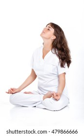 young woman in a white suit sitting in the Lotus position. the doctor meditates