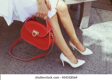 Young woman in white summer classic leather high heel shoes with bright red leather handbag. Girl in a white dress with glitter tattoo on her leg resting on the summer terrace. Handbag fashion look