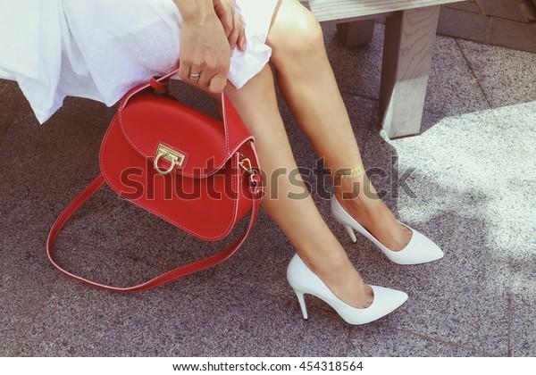 白い夏の古風な革の高いヒール靴を履いた若い女性で、鮮やかな赤い革のハンドバッグを持つ。夏のテラスで休む脚にキラキラ輝くタトゥーを着た白いドレスを着た女の子。ハンドバッグのファッションルック