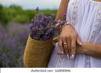 young woman in a white sundress carries a bouquet of lavender in a basket