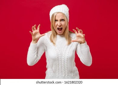 Young woman in white sweater hat isolated on red wall background in studio. Healthy fashion lifestyle cold season concept. Mock up copy space. Shouting, growling like animal, making cat claws gesture