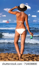 Young woman in white swimsuit and hat holding glass of cold fresh cocktail sunbathing at sea shore.