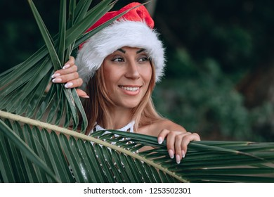 241f78b179950 Young woman in white swimsuit and santa hat on tropical beach smiles at the  camera and