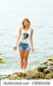 A young woman in a white t shirt with Yin Yang and denim shorts on the rocky shore of the black sea. Joyous stands in the water and shouts