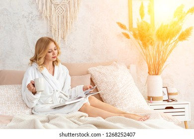 Young woman in white terry robe is drinking coffee and reading magazine or book in bedroom.
