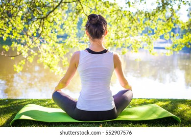 Young woman in white top practicing yoga in beautiful nature.