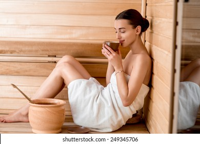 Young woman in white towel drinking tea sitting in Finnish sauna