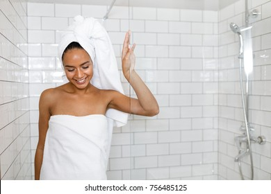 Young woman in white towels wrapped around head and body after shower