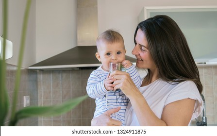 Young woman in white t-shirt playing with her baby son  and drinks green smoothie in blender at home in the kitchen