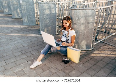 "Young woman in white T-shirt with word ""less"" working for laptop and drinking coffee"