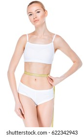 Young woman in white underwear measuring her waist with measuring tape
