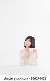 Young woman who thinks about something while drinking tea
