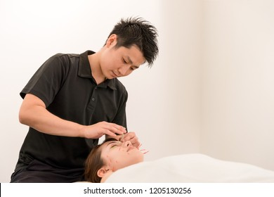 Young woman who undergoes beauty acupuncture · a man of acupuncturist