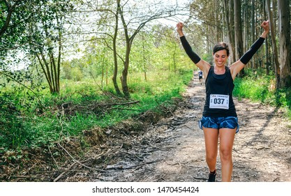 Young woman winning a trail race in the forest